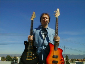 Alex Masi, acclaimed artist & Grammy nominee, is holding is an EXG-PRO  and EXB-4PRO bass.